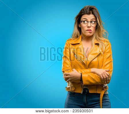 Beautiful young woman nervous and scared biting lips looking camera with impatient expression, pensive, blue background