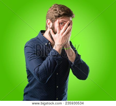 Young hipster man with big beard smiling having shy look peeking through her fingers, covering face with hands looking confusedly broadly over green background