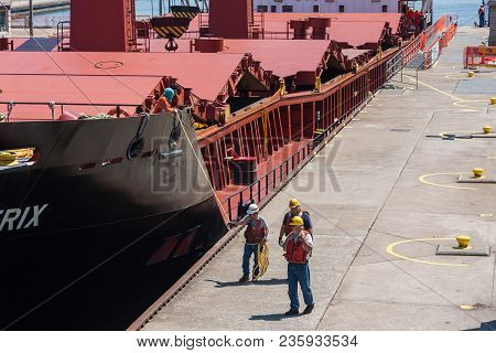 Sault Ste. Marie, Michigan/usa - June 26th, 2013: Group Of Workers Walking Beside Large Ship As It P
