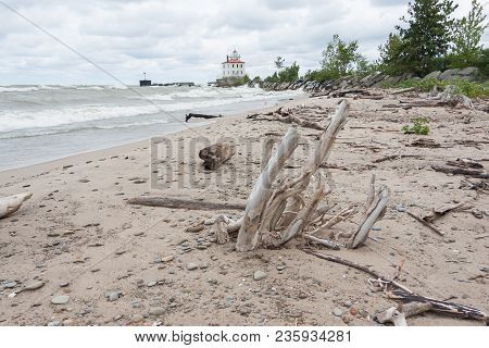 Driftwood And Other Debris On A Beach With A Lighthouse In The Background.