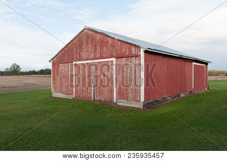 Faded Red Barn On Grassy Lot In The Country.