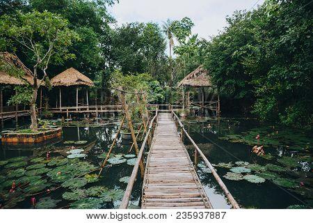 Wooden Footbridge And Lotus Flowers In Pond In Beautiful Park, Hue, Vietnam