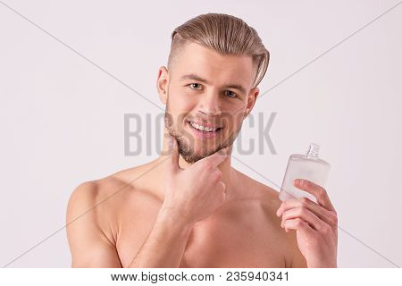Attractive young man applying aftershave lotion on face and smiling while standing isolated on white background. Cheerful bearded hipster holding after shave cream bottle in hand and touching chin