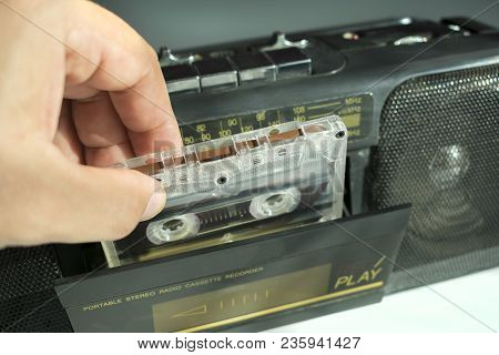Insert Audio Cassette Tape Into A Tape Recorder Hand On White Background Close-up