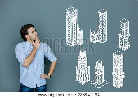 Skyscrapers. Clever qualified experienced architect thoughtfully looking into the distance while planning his work at the skyscraper poster