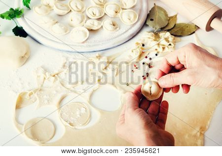 Traditional Russian Pelmeni, Ravioli, Dumplings With Meat On Black Concrete Background. Parsley, Qua