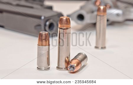 Four Bullets, Two 9mm And Two .357 Magnum With A Stainless .357 Revolver And A Black 9mm Pistol In T