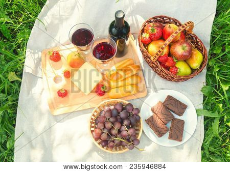 Outdoor Picnic Setting With Red Wine, Cheese, Fruits And Cakes. Top View.