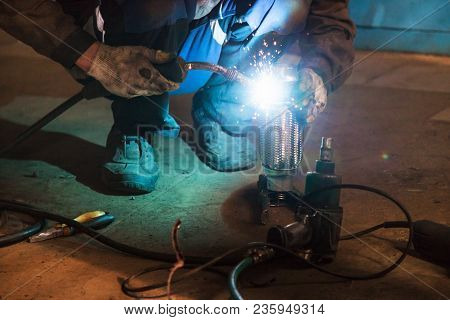Repairing Of Corrugation Muffler Of Exhaust System In Car Workshop - Mechanic Welds The Pipe On Corr