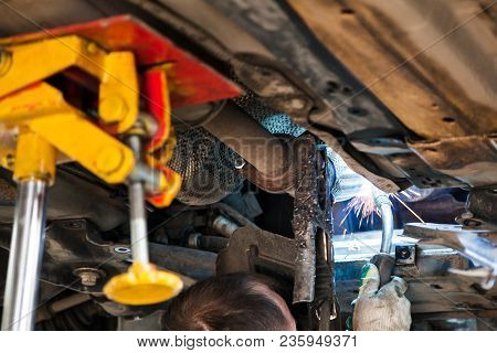 Repairing Of Corrugation Muffler Of Exhaust System In Car Workshop - Worker Welds The Silencer On Ca