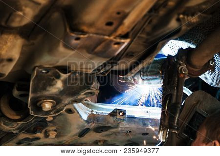 Repairing Of Corrugation Muffler Of Exhaust System In Car Workshop - Welder Welds The Silencer On Ca