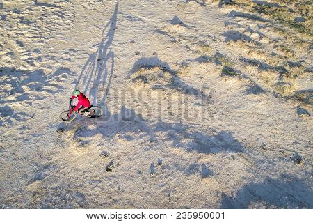 Riding a fat bike on a desert trail, aerial view with a long shadow