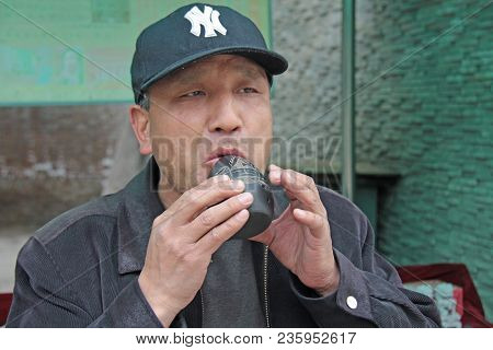China, Beijing - April 12, 2012.traditional Chinese Musical Instrument Xun. A Man Is Playing A Music
