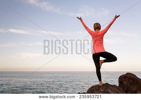 Woman Meditating In Yoga Vrksasana Tree Pose Silhouette At The Ocean, Beach And Rock Mountains. Moti