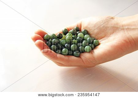 Natural Green Jade Nephrite Mineral Stones Beads. The Green Jade Stone Lies In The Hands. Hands Hold