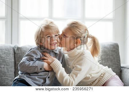 Older Sister Embracing Little Younger Brother At Home, Kid Girl Kissing Cute Shy Smiling Preschool B