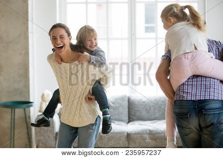 Happy Mother Laughing Piggybacking Little Son Playing With Family At Home, Cheerful Parents Carrying