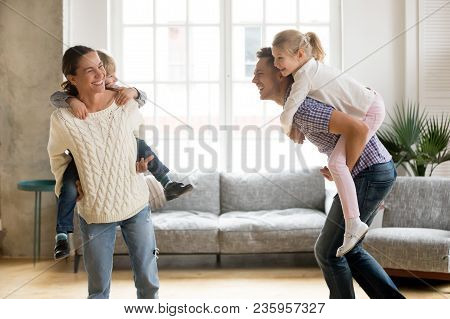 Laughing Parents Holding Kids On Back Giving Children Piggyback Ride Playing Together At Home, Cheer