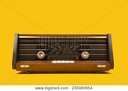 Old Antique Radio Seen From The Front On A Yellow Background