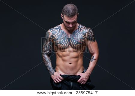 The Man With A Muscular Naked Torso With Tattoos On The Dark Background. Abs.