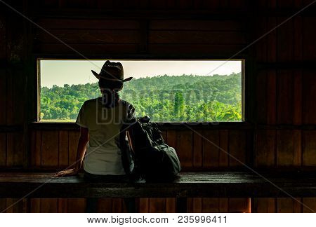 Young Asian Woman Wear The Hat Sit On Wooden Bench And Watching Beautiful View Of Tropical Forest At