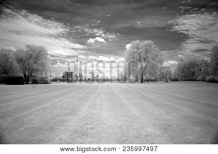 Vast Open Mewed Meadow Surrounded By Trees In Summer In Infrared In Black And White