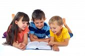Three young children lie down on the floor smiling as they read a book together. poster