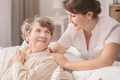 Helpful, young, pretty nurse supporting a lovely older lady with alzheimer in a retirement home poster