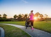 Beautiful, fit women walking and jogging outdoors along a paved sidewalk in a park pushing a stroller at sunset poster