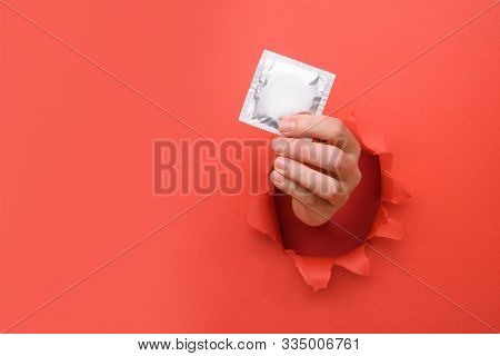 Hand Give Condom On Torn Red Paper Wall. Safe Pleasure And Protection, Contraception, Protection Fro