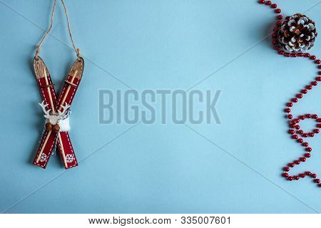 Wooden Toy Ski And Christmass Decoration. Blue Paper Craft Background. Flat Lay. Copy Space