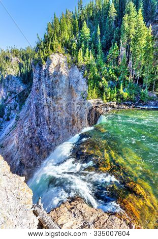 Brink Of Lower Falls At Yellowstone National Park Showing Rushing Waters From The Yellowstone River