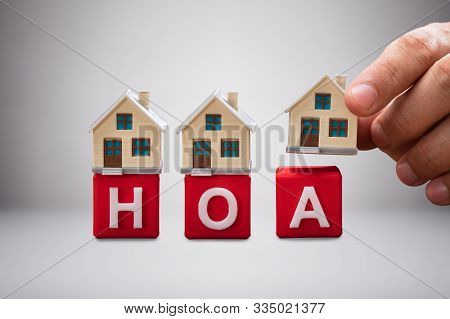 Close-up Of House Miniature Models Over Red Homeowner Association Wooden Blocks Against White Backgr