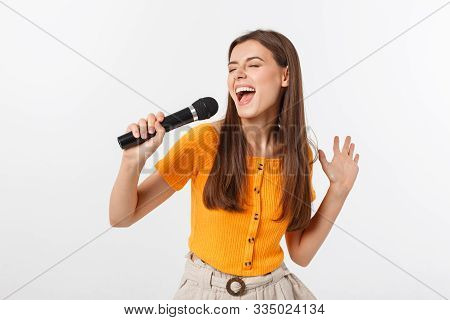Young Pretty Woman Happy And Motivated, Singing A Song With A Microphone, Presenting An Event Or Hav