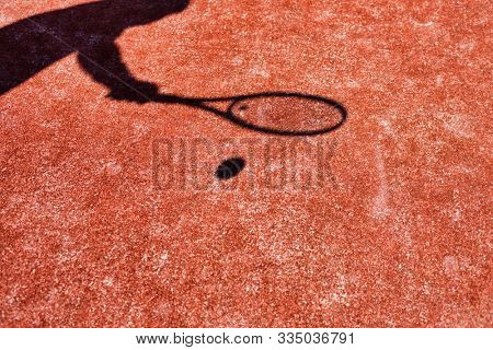 Shadow of athelete playing tennis in court