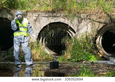 A Specialist In A Gray Protective Suit And Mask, On A Pond, Calls On A Mobile Phone To The Managemen