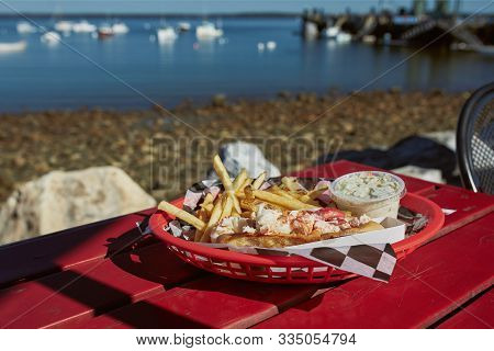 Eating Traditional Maine Lobster Roll With Coleslaw And French Fries On A Waterfront Harbor In Maine
