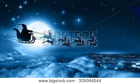 Santa Claus In A Sleigh And Reindeer Sled Flies Over Earth On Background Of Full Moon In Night Winte