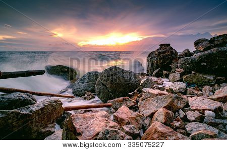 Ocean Water Splash On Rock Beach With Beautiful Sunset Sky And Clouds. Sea Wave Splashing On Stone A