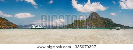 Cadlao Island Background With Filippino Traditional Boats In Shallow Bay At El Nido Bay From Low Ang