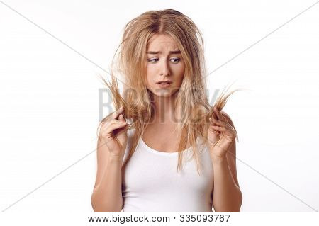 Pretty Young Woman Having A Bad Hair Day Standing Looking Dejectedly At The Dry Ends Of Her Tousled