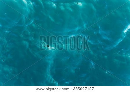 Top View Of A Calm Deep Blue Sea With Ripples On The Water Surface.