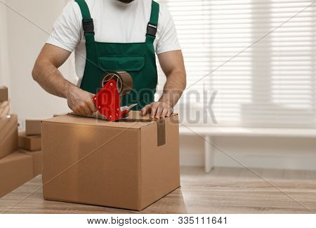 Man Packing Box With Adhesive Tape Indoors, Closeup. Moving Service