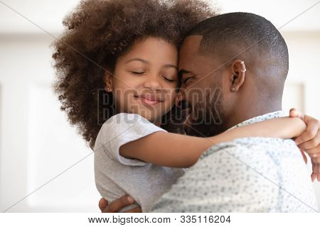 Happy Biracial Dad And Daughter Cuddle At Home