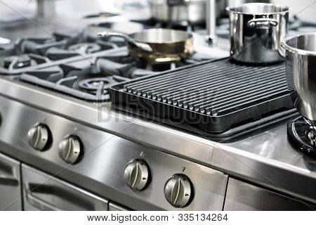 Part Of A Modern Kitchen In The Restaurant Or Hotel With Professional Equipments - Steel Gas Cooker,