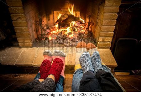 Mother Father And Kids Sitting At Cosy Fireplace On Christmas Time - Lovely Family Resting Together