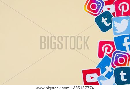 Many Social Network Printed Icons Lies In Pile On Beige Background With Copy Space. Facebook Instagr
