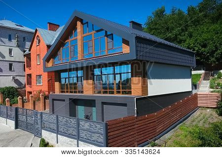 House With A Gray Metal Roof And Large Windows On The Facade. Modern Roof Made Of Metal. Corrugated