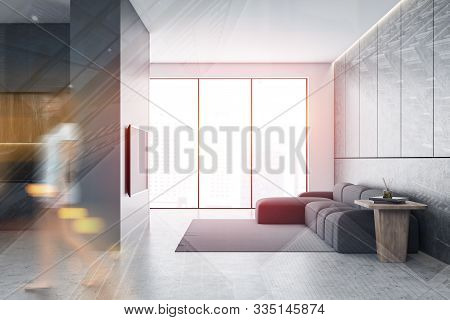 Blurry Young Woman Walking In Modern Living Room With Gray And White Walls, Panoramic Window, Comfor