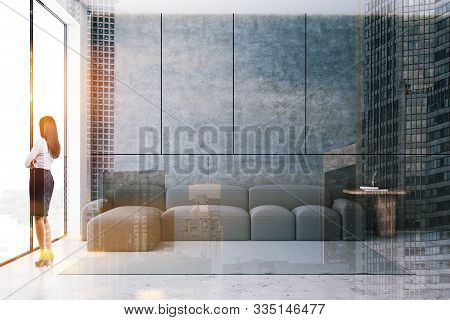 Young Businesswoman Standing In Minimalistic Living Room With Concrete Walls And Floor, Panoramic Wi